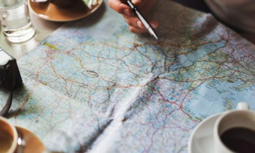 planning trips on a map with a coffee mug and camera